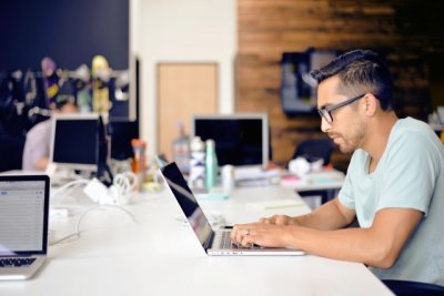 Bad posture - Man slouching over a laptop Bad posture - Man slouching over a laptop